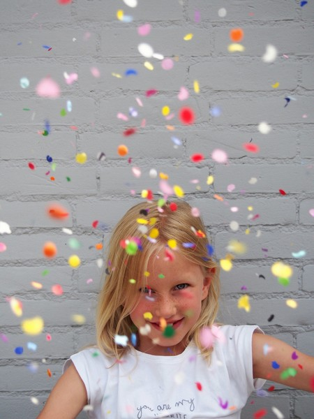 A girl throwing confetti