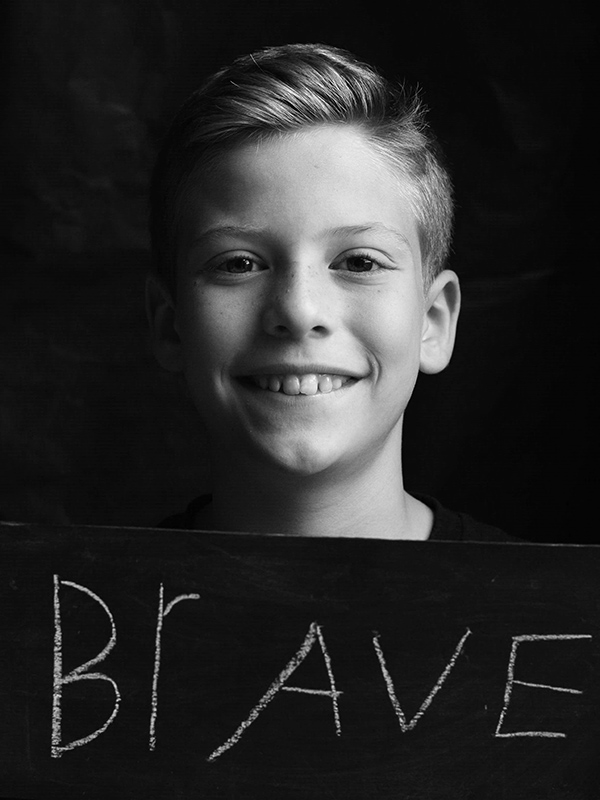 "A boy with a sign that says ""Brave."""
